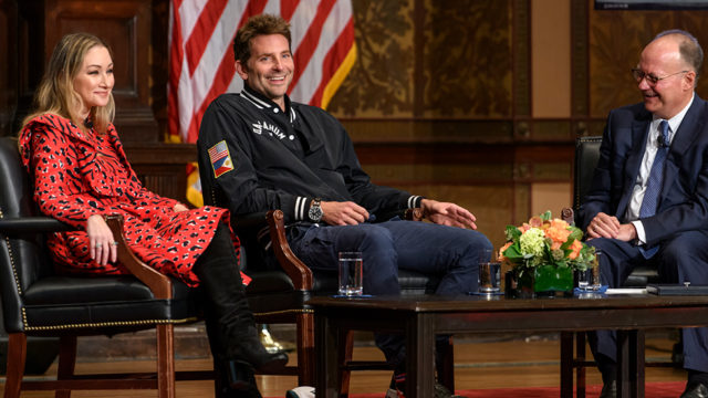 Georgetown President John J. DeGioia sits and talks to Bradley Cooper and Blair Rich on stage in Gaston Hall.