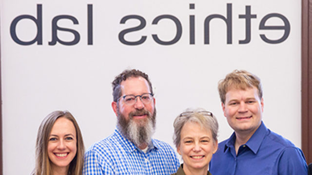 Nitin Vaidya, Ray Essick, Maggie Little, Mark Maloof, Elizabeth Edenberg and Jonathan Healy standing in front 的 the Ethics Lab sign.