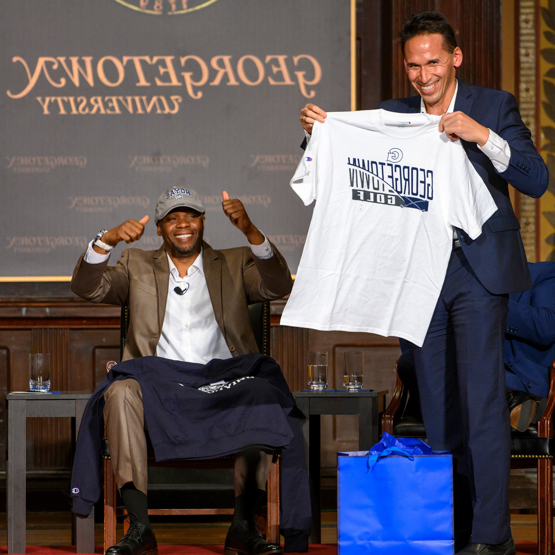 Professor Marc Howard stands on stage in Gaston Hall, presenting a 乔治城大学 golf t-shirt to Valentino Dixon.