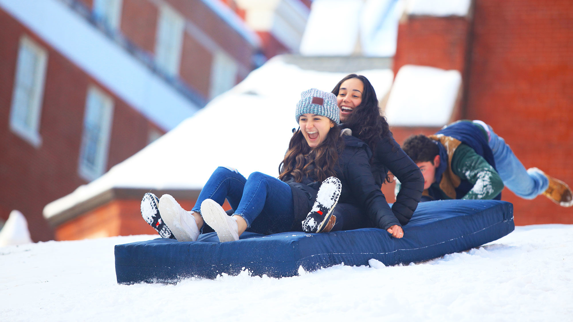 Two students sled down a hill on a mattress.