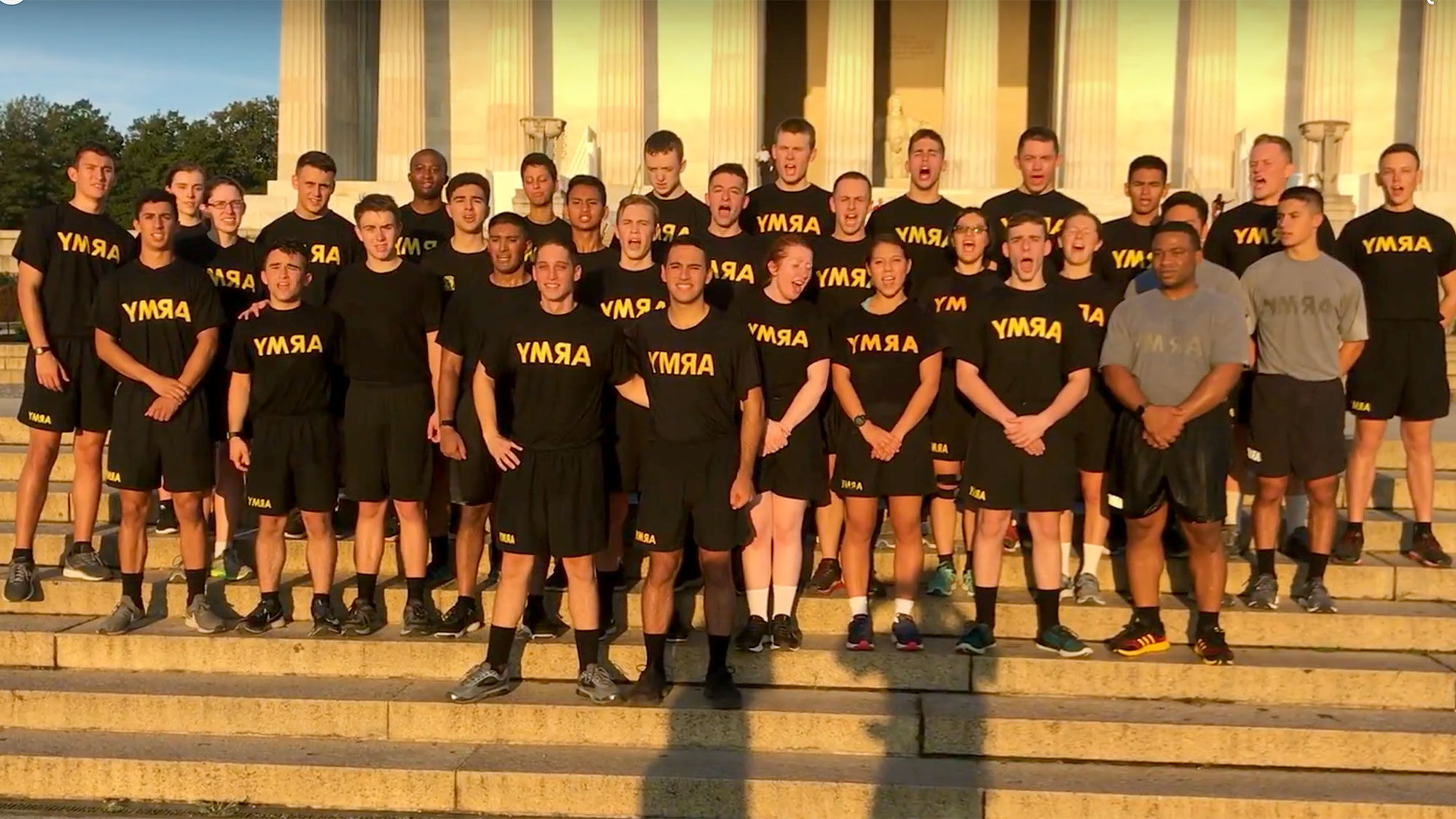 ROTC members dressed in running gear stand on steps with the sun rising in the background.